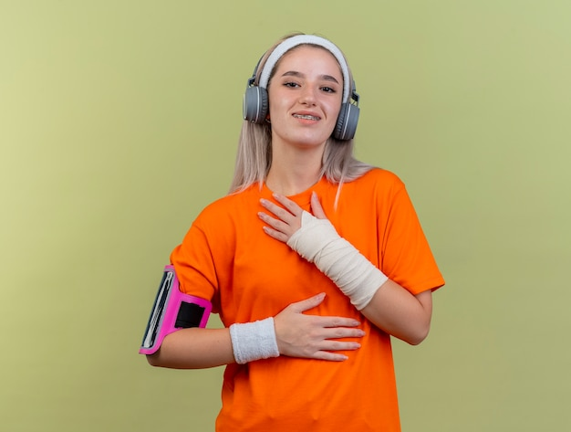 Uśmiechnięta młoda kaukaska sportowa dziewczyna z szelkami na słuchawkach nosząca opaski na nadgarstki i opaskę na telefon kładzie rękę na klatce piersiowej