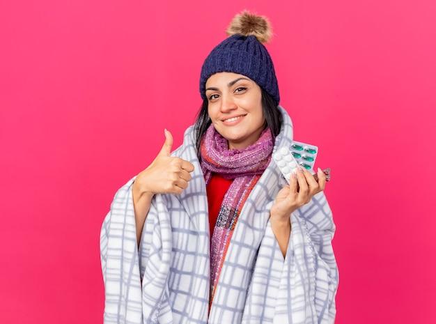 Uśmiechnięta młoda kaukaski chora dziewczyna w czapce zimowej i szaliku owinięta w kratę, patrząc na kamerę trzymającą paczki pigułek pokazującą kciuk w górę na białym tle na szkarłatnym tle z miejscem na kopię