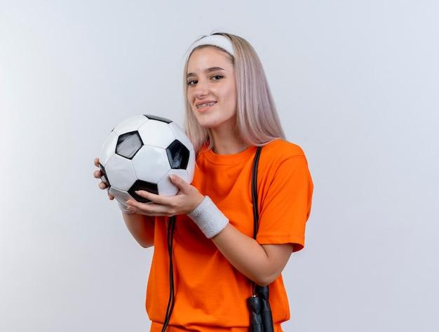 Uśmiechnięta młoda kaukaski dziewczyna sportowa z szelkami i skakanką na szyi, nosząc opaskę i opaski na nadgarstek, trzyma piłkę na białym tle