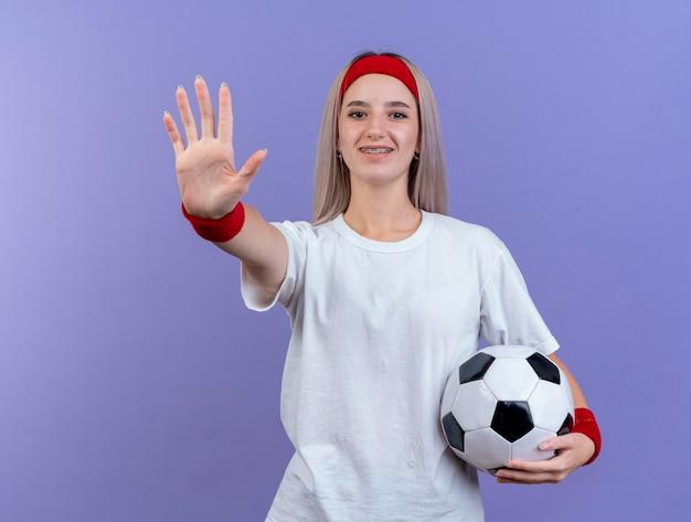 Uśmiechnięta młoda kaukaski dziewczyna sportowy z szelkami na sobie pałąk