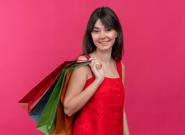 Uśmiechnięta młoda kaukaski dziewczyna trzyma paczki, rzucając je na ramię na na białym tle różowym