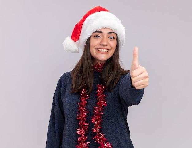 Uśmiechnięta młoda kaukaski dziewczyna z santa hat i girlandą wokół szyi kciuki do góry