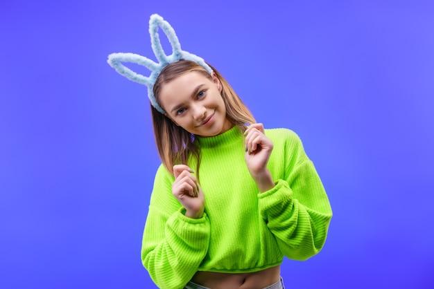 Uśmiechnięta młoda kaukaski kobieta, blondynka z niebieskimi uszami królika i zielonym swetrem, patrząc na kamerę odizolowaną na niebieskiej ścianie