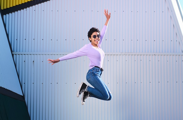 Uśmiechnięta młoda kobieta afro skoki