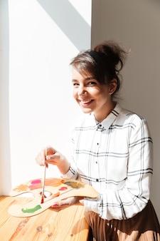 Uśmiechnięta młoda kobieta artysty mienia paleta