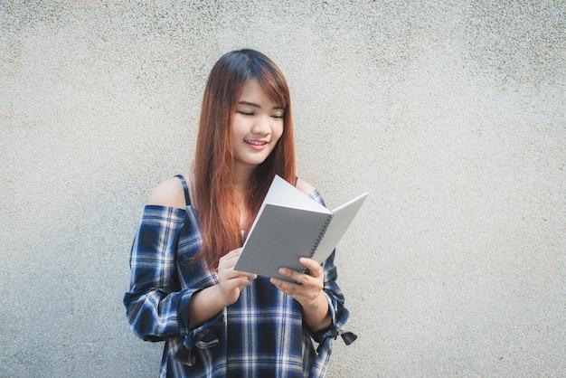 Uśmiechnięta młoda kobieta azjatyckich piękne z książki. closeup br? zowy g? owy pi? kna m? oda kobieta szcz ?? liwy czytania na? cian? obrazy stylu efektów klasycznych.