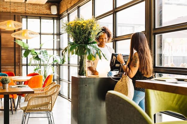 Uśmiechnięta młoda kobieta bierze rozkaz od żeńskiego klienta w restauraci