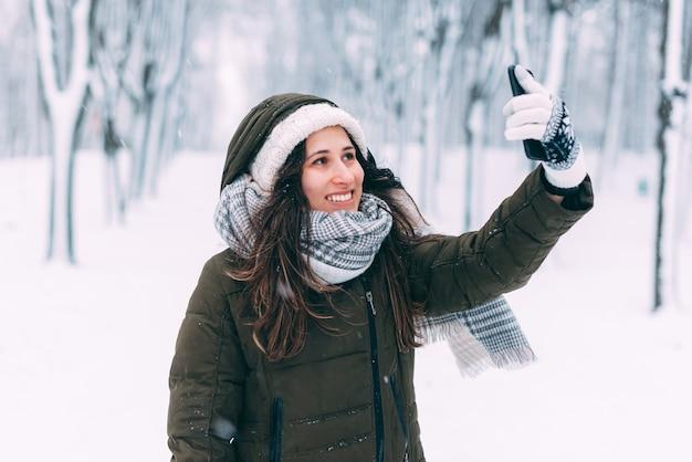 Uśmiechnięta młoda kobieta bierze selfie w lesie pokrytym śniegiem