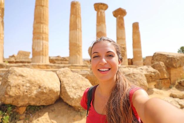 Uśmiechnięta młoda kobieta, biorąc autoportret z grecką świątynią na tle w dolinie świątyń w agrigento, włochy