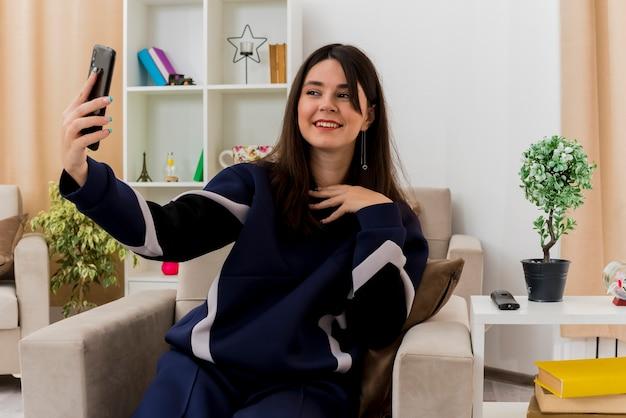 Uśmiechnięta młoda kobieta całkiem kaukaski siedzi na fotelu w zaprojektowanym salonie, dotykając klatki piersiowej i biorąc selfie