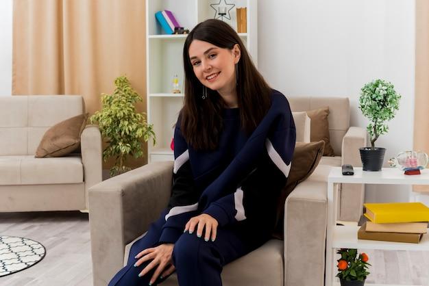 Uśmiechnięta młoda kobieta całkiem kaukaski siedzi na fotelu w zaprojektowanym salonie kładąc ręce na nogach i patrząc