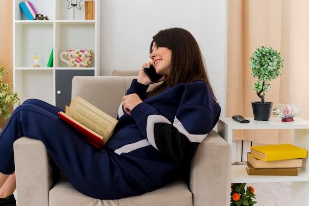 Uśmiechnięta młoda kobieta całkiem kaukaski siedzi na fotelu w zaprojektowanym salonie patrząc prosto rozmawia telefon z książką na nogach