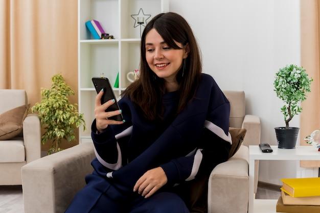 Uśmiechnięta młoda kobieta całkiem kaukaski siedzi na fotelu w zaprojektowanym salonie, trzymając i patrząc na telefon komórkowy