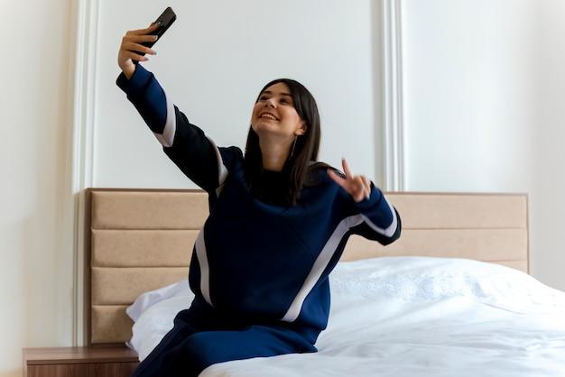 Uśmiechnięta młoda kobieta całkiem kaukaski siedzi na łóżku w sypialni robi znak pokoju i biorąc selfie
