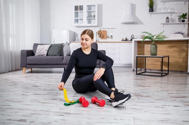 Uśmiechnięta młoda kobieta ćwiczenia z gumką w domu treningu fitness. pojęcie zdrowego stylu życia. sport w domu podczas kwarantanny