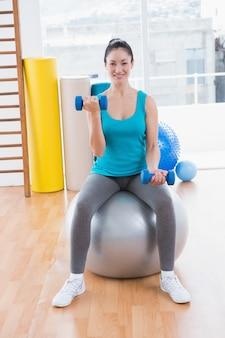 Uśmiechnięta młoda kobieta ćwiczy z dumbbells na sprawności fizycznej piłce