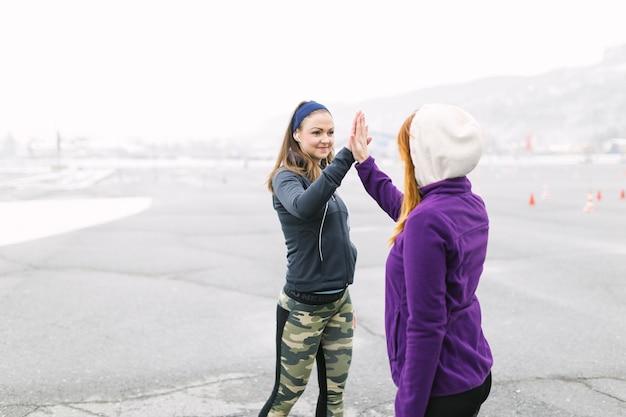 Uśmiechnięta młoda kobieta daje wysokości pięć jej przyjaciel przy outdoors