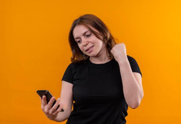 Uśmiechnięta młoda kobieta dorywczo trzymając telefon komórkowy i patrząc na niego z podniesioną pięścią na odosobnionej pomarańczowej przestrzeni