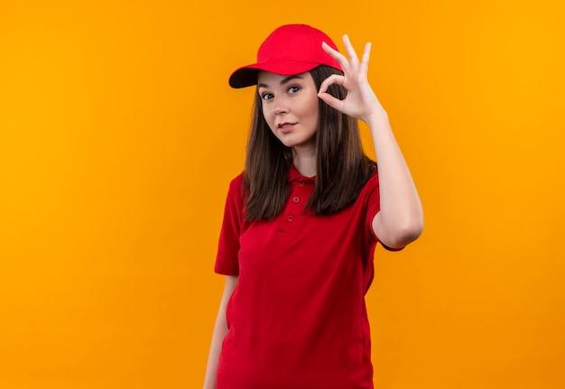Uśmiechnięta młoda kobieta dostawy na sobie czerwoną koszulkę w czerwonej czapce i pokazuje okey gasture na odizolowanej żółtej ścianie
