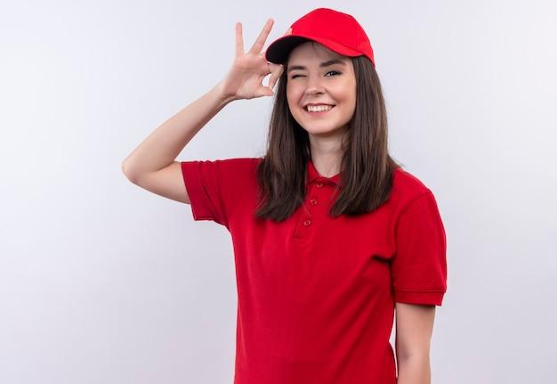 Uśmiechnięta młoda kobieta dostawy na sobie czerwoną koszulkę w czerwonej czapce miga na odizolowanej białej ścianie