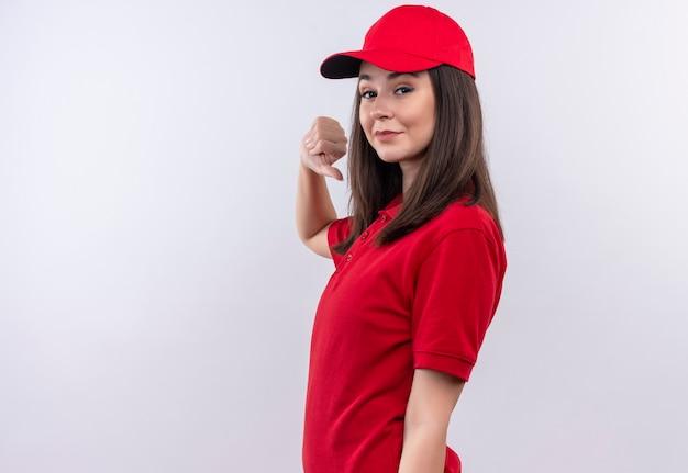 Uśmiechnięta młoda kobieta dostawy na sobie czerwoną koszulkę w czerwonej czapce pokazując kciuk w dół na odosobnionej białej ścianie