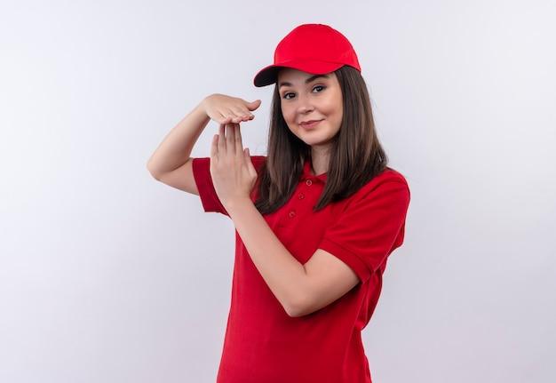 Uśmiechnięta młoda kobieta dostawy na sobie czerwoną koszulkę w czerwonej czapce pokazuje limit czasu na na białym tle białej ścianie