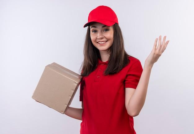 Uśmiechnięta młoda kobieta dostawy na sobie czerwoną koszulkę w czerwonej czapce trzyma pudełko i podniósł rękę na odizolowanej białej ścianie