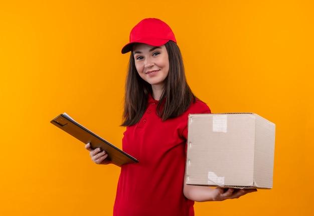 Uśmiechnięta młoda kobieta dostawy na sobie czerwoną koszulkę w czerwonej czapce trzyma pudełko i schowek na odizolowanych żółtej ścianie