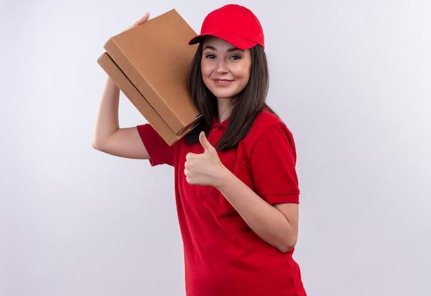 Uśmiechnięta młoda kobieta dostawy na sobie czerwoną koszulkę w czerwonej czapce trzyma pudełko po pizzy i pokazuje kciuki do góry na odosobnionej białej ścianie