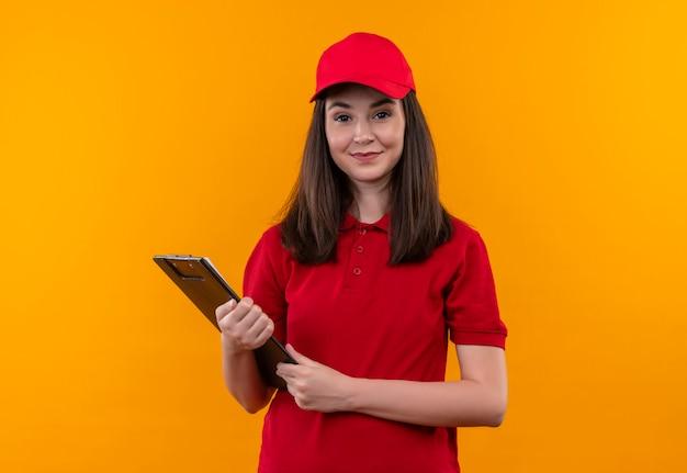 Uśmiechnięta młoda kobieta dostawy na sobie czerwoną koszulkę w czerwonej czapce trzyma schowek na odizolowanych żółtej ścianie