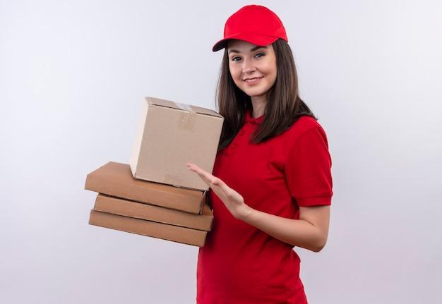 Uśmiechnięta młoda kobieta dostawy na sobie czerwoną koszulkę w czerwonej czapce, trzymając pudełko i pudełko po pizzy na odizolowanej białej ścianie