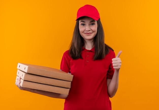 Uśmiechnięta młoda kobieta dostawy ubrana w czerwoną koszulkę w czerwonej czapce trzyma pudełko po pizzy i pokazuje jak na odizolowanej pomarańczowej ścianie