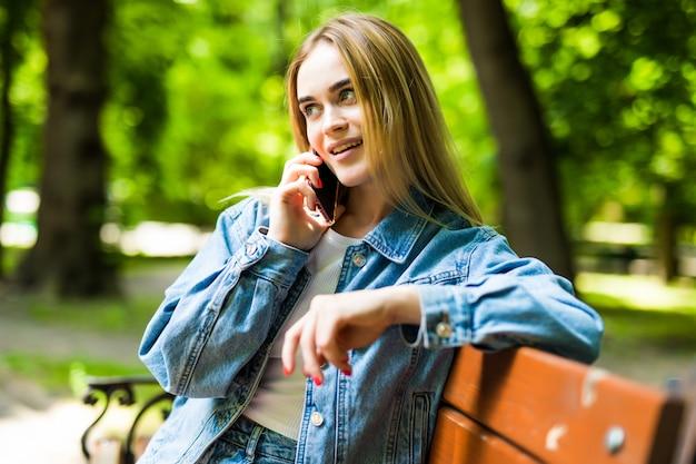 Uśmiechnięta młoda kobieta dzwoni na smartphone na miasto ulicie