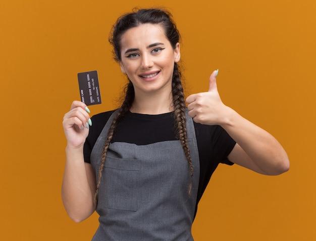 Uśmiechnięta młoda kobieta fryzjer w mundurze trzyma kartę kredytową pokazując kciuk do góry na białym tle na pomarańczowej ścianie