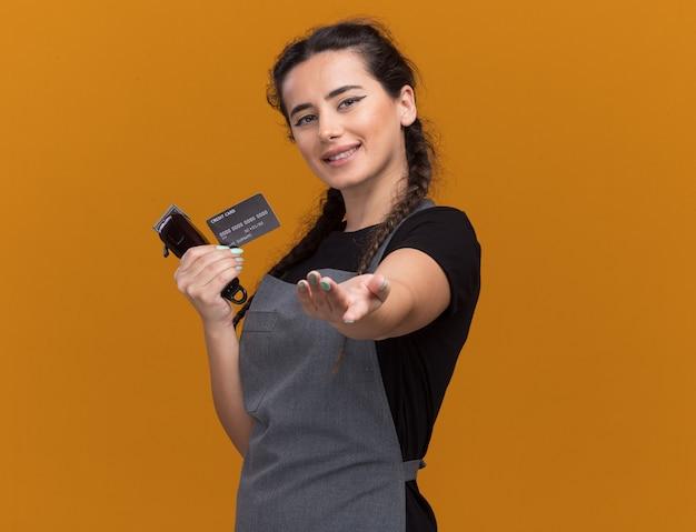 Uśmiechnięta młoda kobieta fryzjer w mundurze, trzymając kartę kredytową i maszynki do strzyżenia włosów, wyciągając rękę na białym tle na pomarańczowej ścianie z miejsca na kopię
