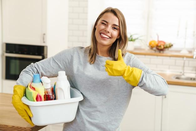Uśmiechnięta młoda kobieta gospodyni domowa w rękawiczkach trzymająca butelki do mycia i pokazująca kciuk w nowoczesnej kuchni