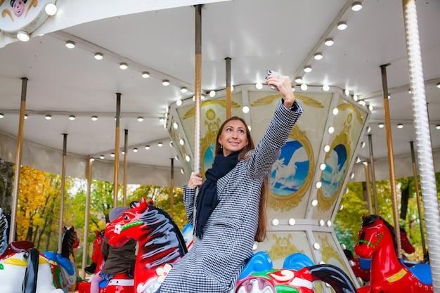 Uśmiechnięta młoda kobieta jedzie na koniu na karuzeli w parku rozrywki i robi selfie za pomocą telefonu komórkowego