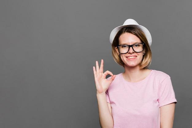 Uśmiechnięta młoda kobieta jest ubranym białego kapelusz pokazuje ok znaka przeciw popielatemu tłu