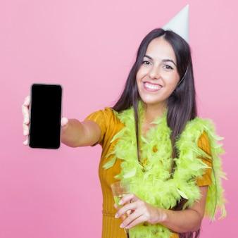 Uśmiechnięta młoda kobieta jest ubranym boa i przyjęcia kapelusz pokazuje smartphone