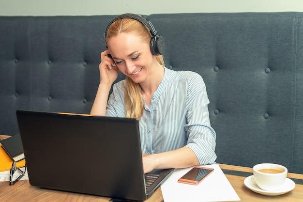 Uśmiechnięta młoda kobieta jest ubranym hełmofony i siedzi przed otwartym laptopem przy stołem w biurze