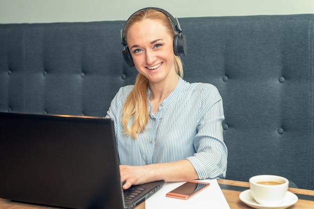 Uśmiechnięta młoda kobieta jest ubranym hełmofony siedzi przed otwartym laptopem przy stołem przy kawiarnią.