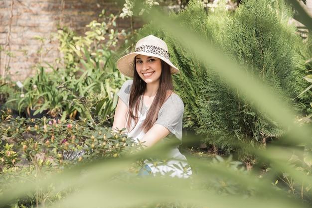 Uśmiechnięta młoda kobieta jest ubranym kapeluszową pozycję w szklarni