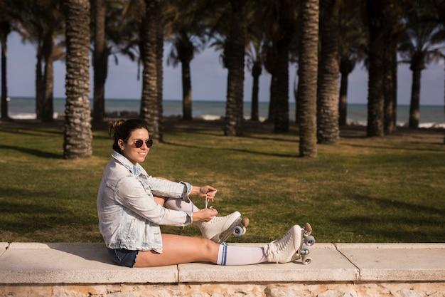 Uśmiechnięta młoda kobieta jest ubranym okulary przeciwsłonecznych wiąże koronkę łyżwa