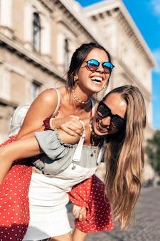 Uśmiechnięta młoda kobieta jeździ na barana koleżance podczas spaceru po ulicy