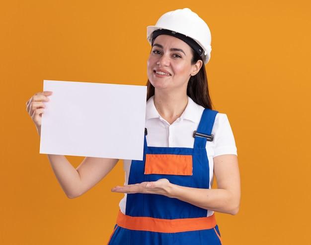 Uśmiechnięta młoda kobieta konstruktora w mundurze gospodarstwa i wskazuje ręką na papier na białym tle na pomarańczowej ścianie
