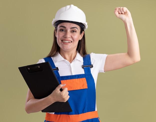 Uśmiechnięta młoda kobieta konstruktora w mundurze gospodarstwa schowka podnosząc pięść na oliwkowej ścianie