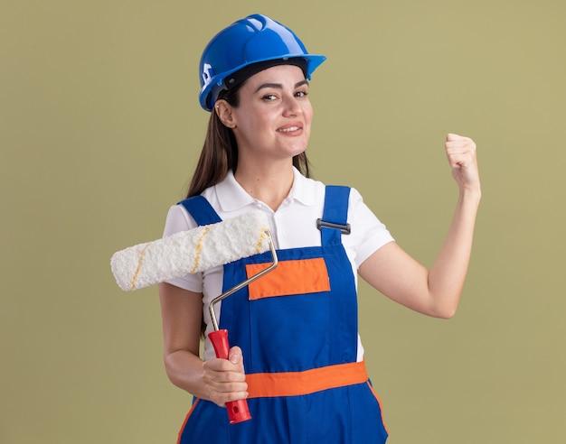 Uśmiechnięta młoda kobieta konstruktora w mundurze, trzymając pędzel rolkowy i pokazując gest tak na białym tle na oliwkowej ścianie