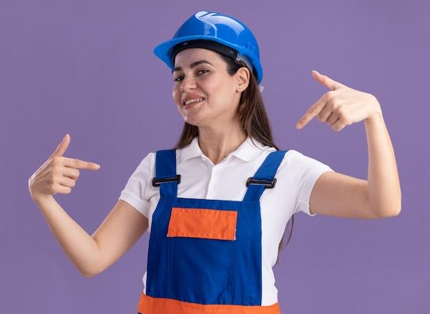 Uśmiechnięta młoda kobieta konstruktora w mundurze wskazuje na siebie na białym tle na fioletowej ścianie