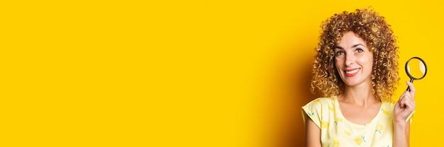 Uśmiechnięta młoda kobieta kręcone z lupą na żółtej powierzchni