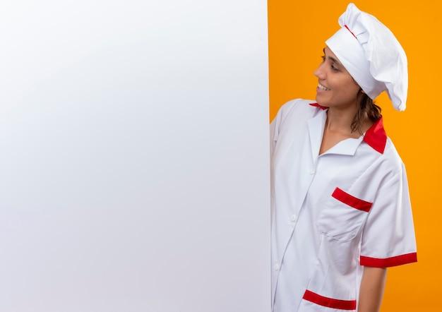 Uśmiechnięta młoda kobieta kucharz ubrana w mundur szefa kuchni i patrząc na białą ścianę z miejsca na kopię